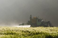 Tractor is spraying pesticides on a field